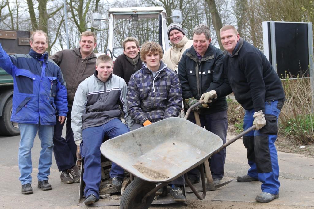 Das Bild zeigt die Sportler, die sich vor einem Traktor mit Schubkarre und Spitzhacke zum Arbeitseinsatz trafen